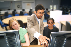 A male tutor aiding students with computer studies