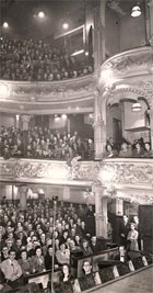 Black and white photograph of the audience at the Metropole Theatre (1862-1961), Stockwell Street, Glasgow c 1950. Side view showing three tiers, one of the boxes and part of the orchestra pit. (STA Ae10/3a-c) Links to collection description.