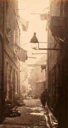 Black and white photograph of children sitting and standing in a narrow back lane, from Thomas Annan's The Old Closes and Streets of Glasgow, produced as a commission from the City of Glasgow Improvements Trust, c 1872. (Sp Coll Dougan 64, plate 13) Links to book of the month article.