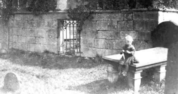An old photo of boy sitting on a tombstone in a graveyard