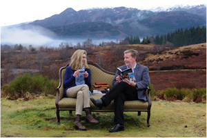 A photograph of Jenni Steele, Head of Partnership Communications at VisitScotland and Professor Alan Riach, Professor of Scottish Literature, sitting on a sofa in the Scottish landscape, holding books and talking.