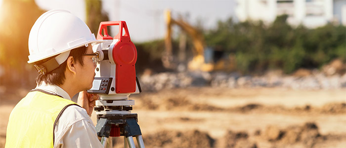 Surveyor engineer is measuring level on construction site
