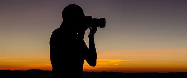 photographer silhouetted against a sunset