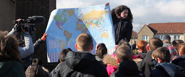 crowd of school children being shown a map of the world