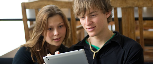 male and female student looking at a tablet computer