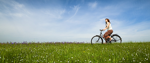 girl cycling in a field