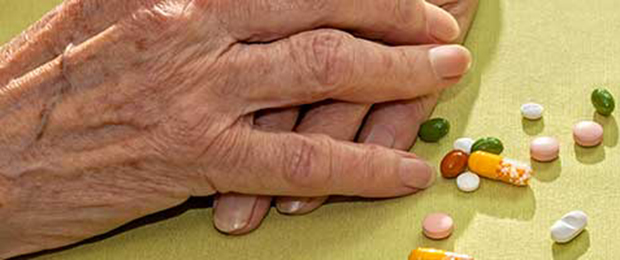 elderly hands with pharmaceutical pills