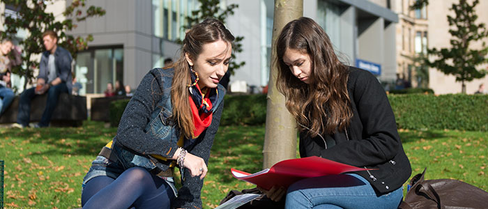 2 students studying outside the library