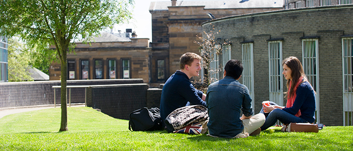 three students sitting on grass outside Glasgow University Reading Room