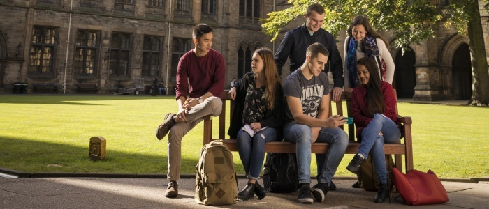 Students sitting on a bench in the quadrangle