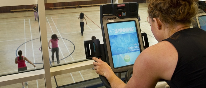 Student using exercise equipment in gym