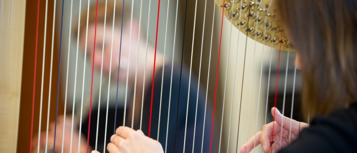 Music student playing harp