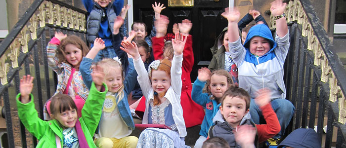 Primary school children sitting on steps waving