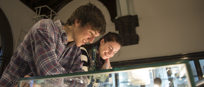 Two students looking in a case in the Hunterian Museum Science Showcase space.