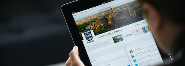 A photograph taken from over a person's shoulder. The person is holding a tablet, on which you can see the University of Glasgow's Twitter profile.