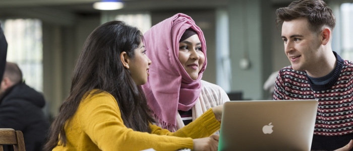 Two female students sitting down and viewing a laptop computer.