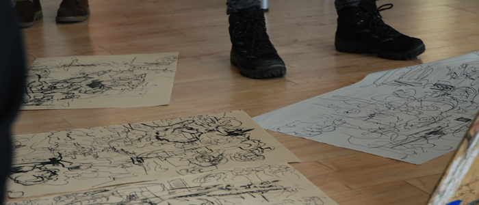 Photograph of a person's boots, standing next to drawings on the floor. Taken at 'Glasgow Kiss', A film and drawing event devised by MLitt Curatorial Practice (Contemporary Art) student Eilidh Ratcliffe, 2014