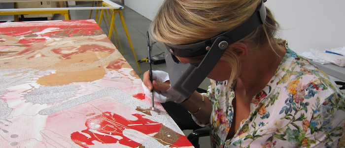 A woman wearing goggles and holding a paintbrush as she carries out conservation work on a contemporary painting.