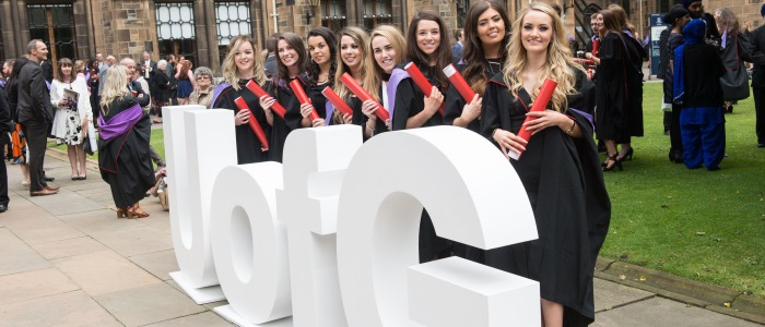 Group of female students at graduation with UofG letters