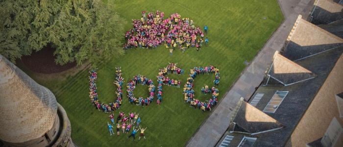 An aerial shot of a large group of people forming UofG in the quadrangle