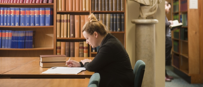 A student sitting in front of bookshelves in the Law Library