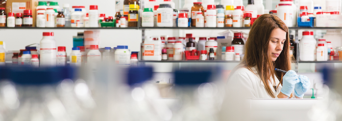Student in lab - backround shelves with colourful bottles and jars