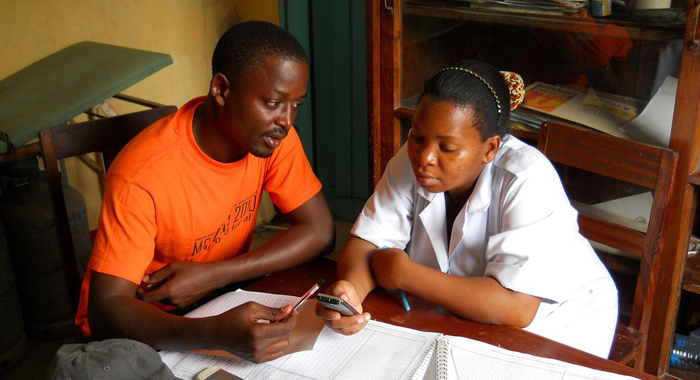 Zac Mtema training a healthworker to use mobile app. Credit Katie Hampson