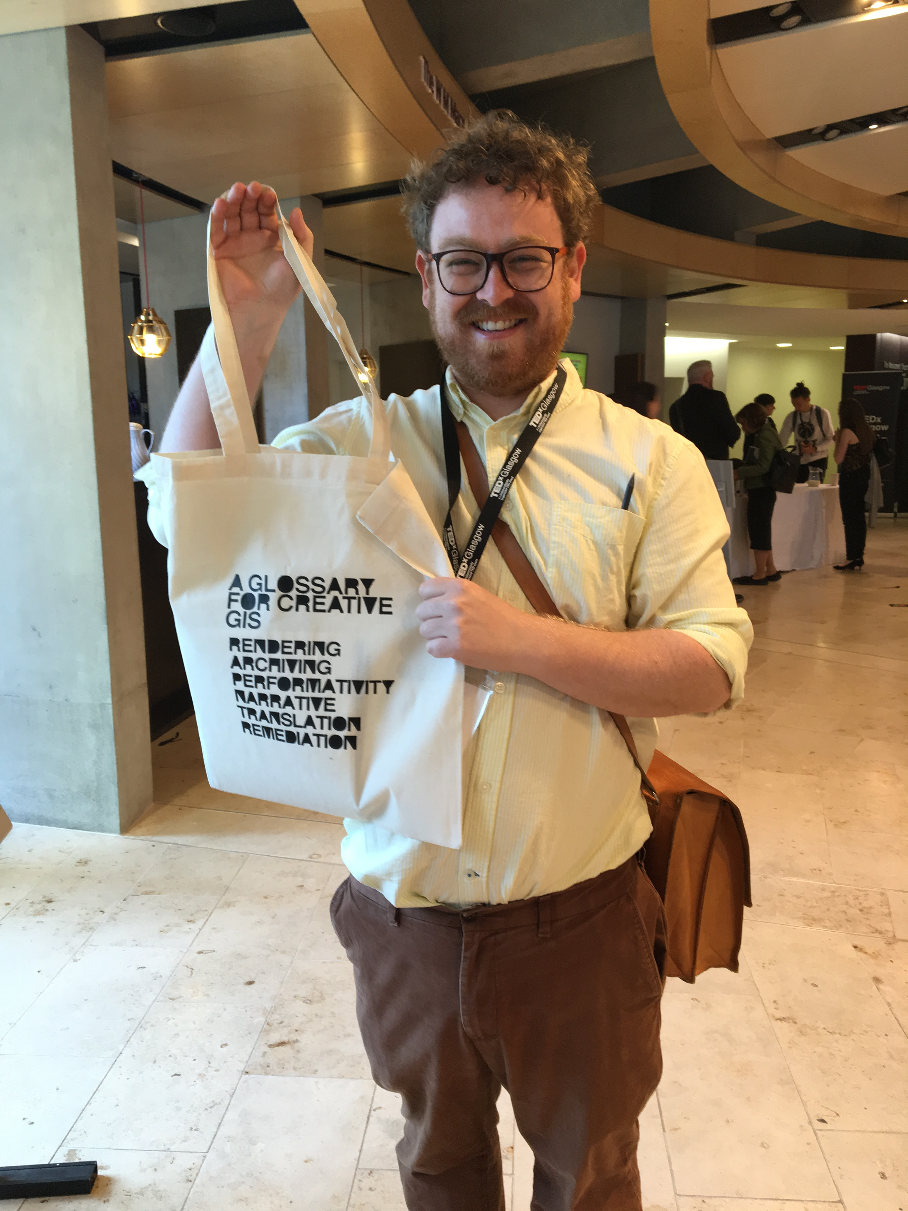 Photo of Phil Nicholson holding tote bag created at TEDx