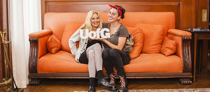 Two women on couch with small UofG