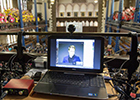 Image of Rector Edward Snowden on a lap-top screen in the Bute Hall