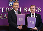 The signatories of the Memorandum of Understanding between UofG and the Universiti Sains Malaysia, shaking hands.