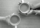 Two people's hands holding mugs of tea