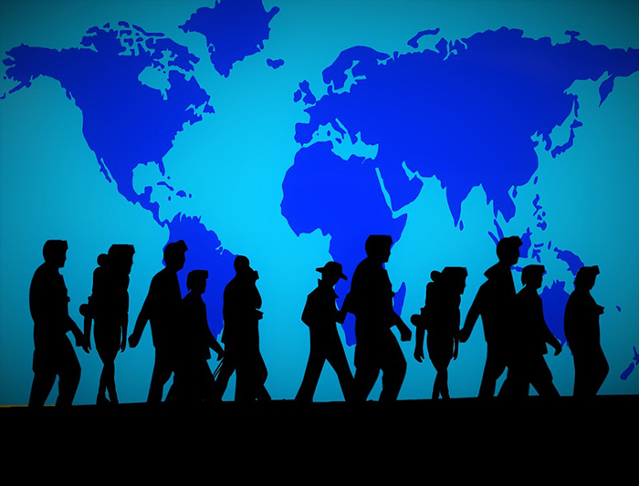 People walking, silhouetted in front of a world map