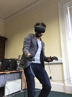 photo of a man in jeans, a blazer and white tshirt, with black beard and curly hear, kitted out with a virtual reality headset and two handheld controllers, moving inside a classroom. in the background there are wires and a computer set up