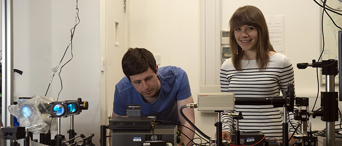 Two researchers smiling as they work with lab equipment