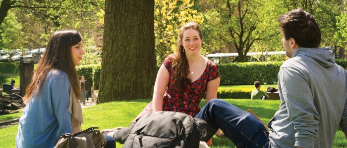 2 female, one male student sitting on grass