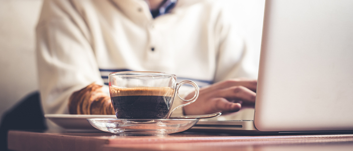 Man sitting at laptop with cup of coffee