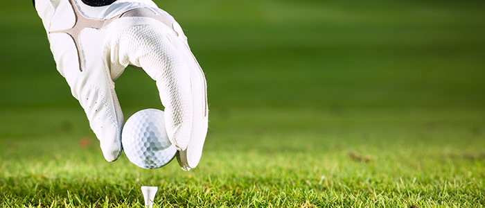 Image of a golf-gloved hand placing a ball on a golf tee.