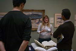 A student stands behind a table in an art gallery talking about the rare book which sits on the table on a protective cushion. Two people are in front of the table listening.