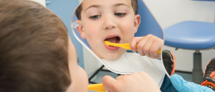 Child cleaning teeth in a mirror