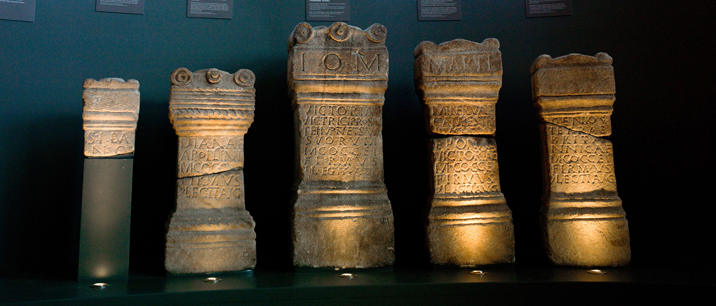Antonine Wall display: 5 carved sandstone altars are shown on a plain black background