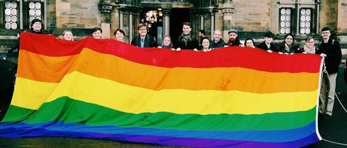 Image of UofG people holding the LGBT+ flag