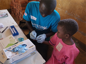 Health worker taking a finger prick blood test in Mayuge District, Uganda