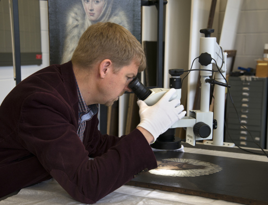 Dr Mark Richter carries out examination with a stereomicroscope of the El Greco Portrait of a Gentleman in the Stirling Maxwell Collection for comparison with the Lady in a Fur Wrap (pictured behind). © CSG CIC Glasgow Museums Collection.