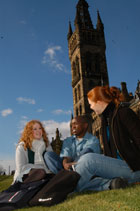 two female and a male student in front of the university tower