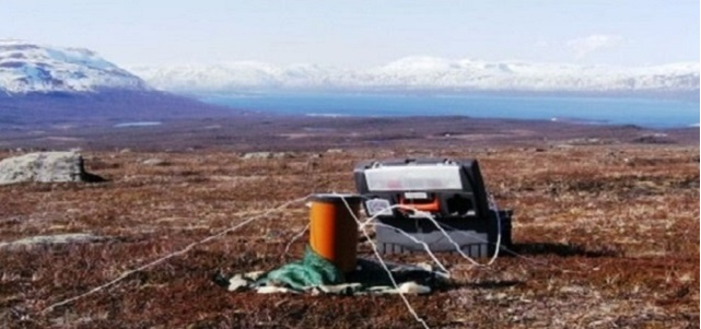Collecting soil respired carbon dioxide from Arctic tundra for radiocarbon analysis.