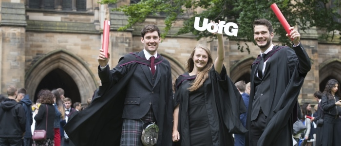 Students during graduation with scrolls and the UofG sign