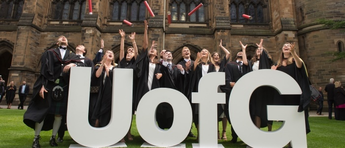 Students during graduation with the UofG sign