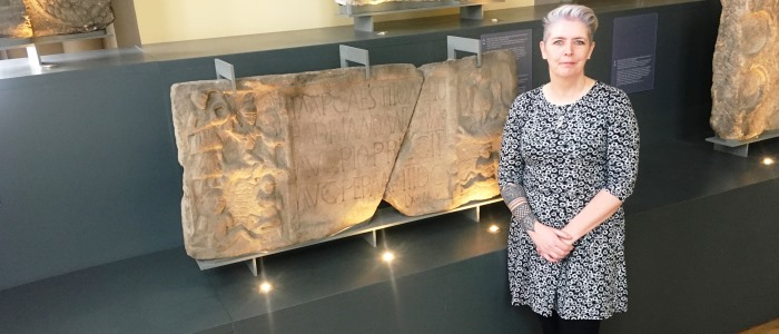 Dr Louisa Campbell in front of Summerston distance stone in The Hunterian