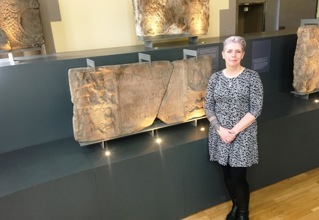 Dr Louisa Campbell in The Hunterian with  one of the Roman stones she examined for paint pigment